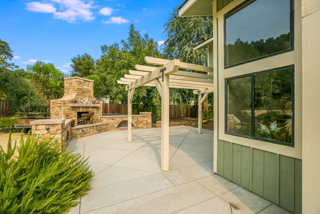patio with pergola and stone fireplace
